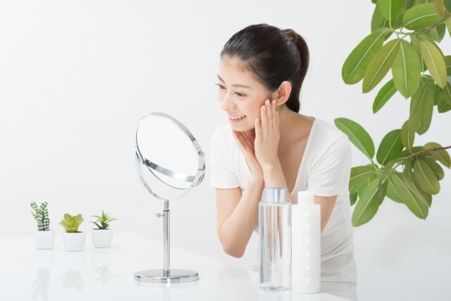 鏡で肌をチェックする女性イメージ